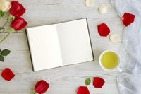 Flatlay of wooden background with roses and journal
