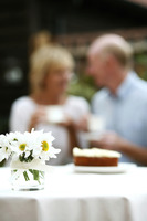 Focus on a vase of flowers with senior couple having tea in the background