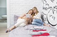 Full-length of mother with daughter using tablet pc in bedroom