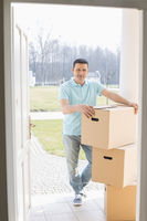 Full-length portrait of man with stacked cardboard boxes at new house