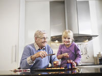 Girl  3-4  and grandfather spreading jam on biscuits in kitchen
