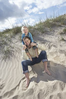Girl  5-6  sitting on father s shoulders on beach portrait
