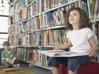 Girl holding open book sitting in library