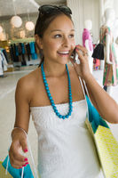 Girl holding using cell phone in clothing store