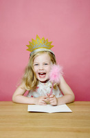 Girl with crown smiling while holding a pencil