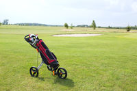 Golf club bag on pushcart at golf course against sky