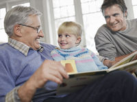 Grandfather reading to girl  3-4  father looking on in house