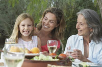 Grandma mother and daughter  5-6  sitting at table in garden girl laughing