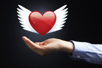Hand presenting a heart shape with wings