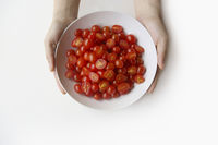 Hands holding a plate of sliced cherry tomatoes