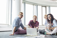 Happy businesspeople looking away while working on floor at creative office