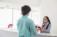 Happy businesswoman giving files to male colleague at counter in creative office
