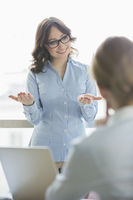 Happy businesswoman talking to businesswoman in office