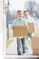Happy father and son with cardboard boxes entering new home