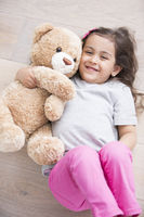 Happy girl with teddy bear lying on wooden floor at home
