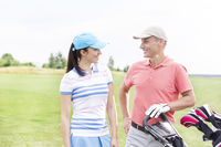 Popular : Happy male and female golfers communicating against clear sky