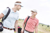 Popular : Happy male golfers conversing against clear sky