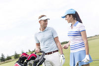 Popular : Happy man and woman conversing at golf course against clear sky