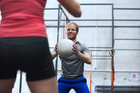 Happy man throwing medicine ball towards woman in crossfit gym