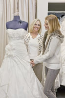 Happy mother and daughter looking at beautiful wedding dress in bridal store