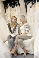 Happy mother and daughter looking at each other while sitting on sofa in bridal boutique