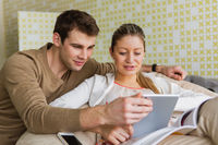 Happy young couple using tablet pc at home