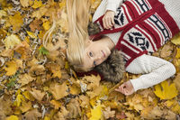 High angle portrait of young woman lying on autumn leaves in park