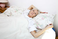 High angle view of senior woman looking away while lying in bed at home