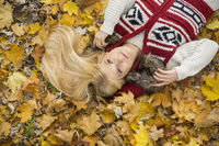 High angle view of thoughtful young woman lying on autumn leaves in park