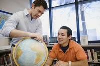 High school teacher pointing out location on globe to student