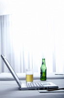 Laptop and beer on the bed