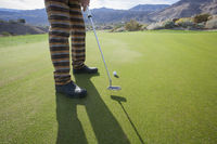 Popular : Low section of senior male golfer playing at golf course