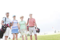Popular : Male and female friends standing at golf course against clear sky
