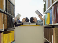 Male and female student lying down on windowsill in library reading