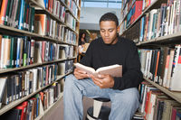 Male student sitting reading in library