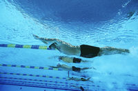 Male swimmers racing in pool underwater view