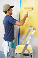 Man applying yellow paint to interior wall
