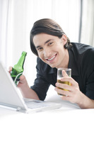 Man drinking beer while using laptop