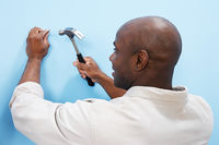 Man hammering nail into wall back view