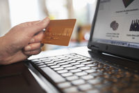 Man holding credit card in front of laptop close up