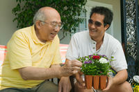 Man holding potted plant talking to father in garden
