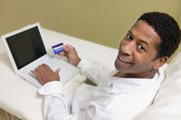 Man on sofa  using credit card to make purchase with laptop portrait high angle view