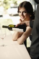 Man pouring wine into woman s glass