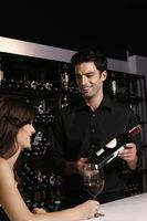 Man recommending a bottle of wine to woman