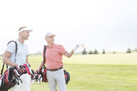 Popular : Man showing something to friend at golf course against clear sky