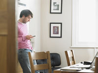 Man standing in kitchen text messaging