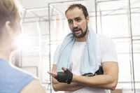 Popular : Man talking to male friend in crossfit gym