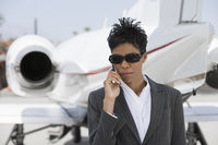 Mid-adult african-american businesswoman standing in front of private plane and talking on phone