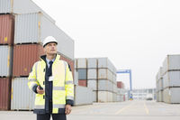 Middle-aged man holding walkie-talkie in shipping yard