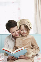 Mother and daughter  5-6  in bedroom reading book girl in bunny costume